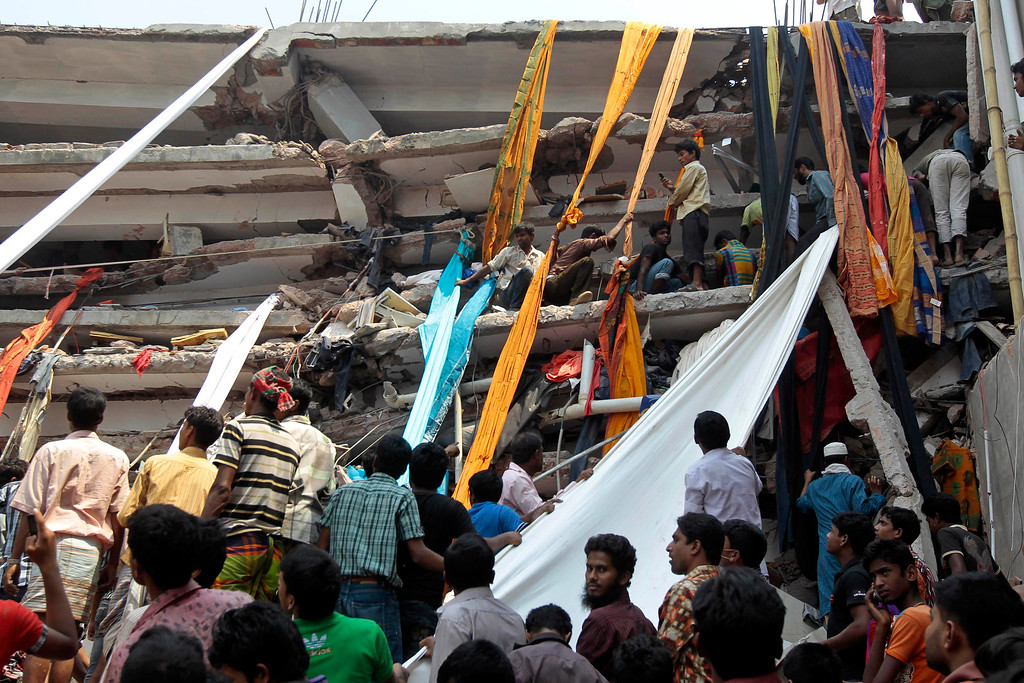 Description of . Rescue workers use clothes to bring down survivors and bodies after an eight-story building housing several garment factories collapsed in Savar, near Dhaka, Bangladesh, Wednesday, April 24, 2013.  (AP Photo/ A.M. Ahad)