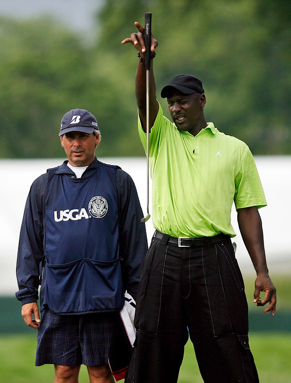 Description of . Michael Jordan, right, lines up a putt with the help of his caddie PGA Tour golfer Fred Couples during the Golf Digest U.S. Open Challenge on Bethpage State Park's Black Course Friday, June 12, 2009 in Farmingdale, N.Y. (AP Photo/Jason DeCrow)