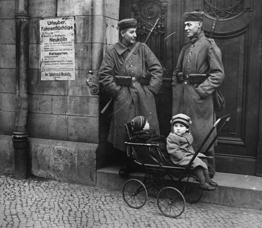 Description of . Policemen looking after children while on duty in Berlin, during the revolution which broke out following Germany's defeat in World War I.   (Photo by Topical Press Agency/Getty Images)