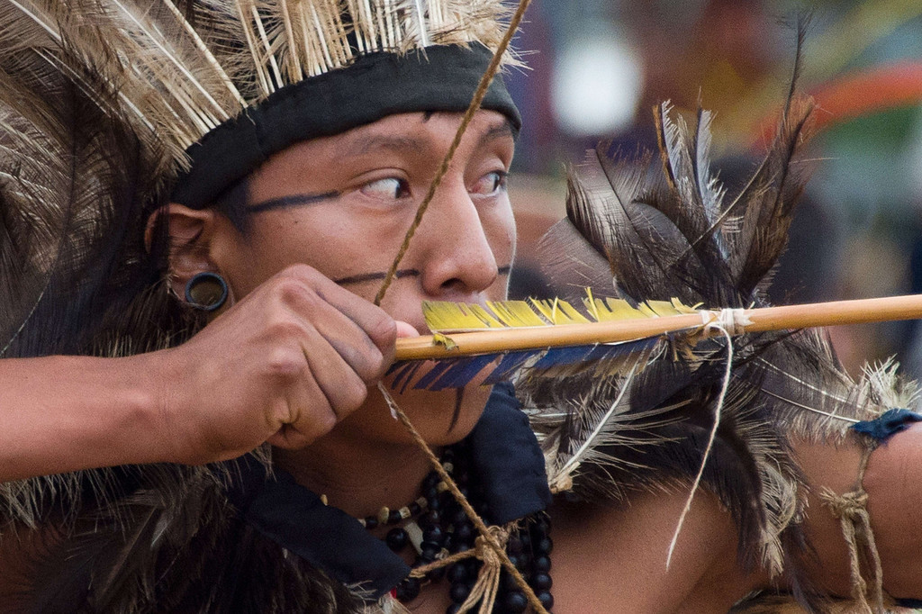 Description of . A Brazilian indigenous man of the Terena tribe takes part in the bow and arrow competition during the XII International Games of Indigenous Peoples in Cuiaba, Mato Grosso state, Brazil on November 12, 2013. AFP PHOTO / Christophe SIMON/AFP/Getty Images