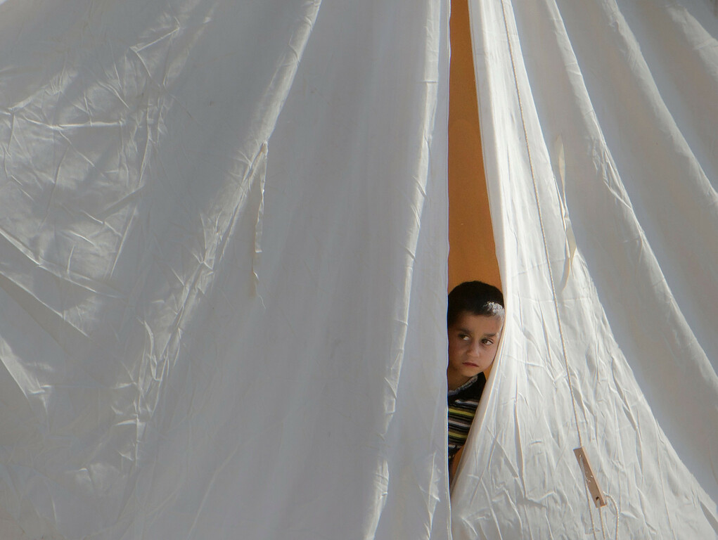 Description of . FILE - A Syrian refugee boy peers from a tent in a camp in Boynuyogun, Turkey, Tuesday, June 14, 2011. (AP Photo/Vadim Ghirda, File)