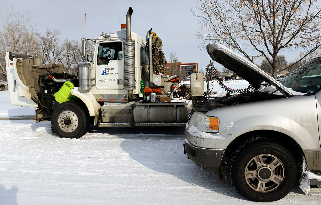 Description of . With temperatures hovering around zero degrees, Jon Willden works to get his semi truck running Wednesday morning Feb. 05, 2014.(Lewis Geyer/Times-Call)
