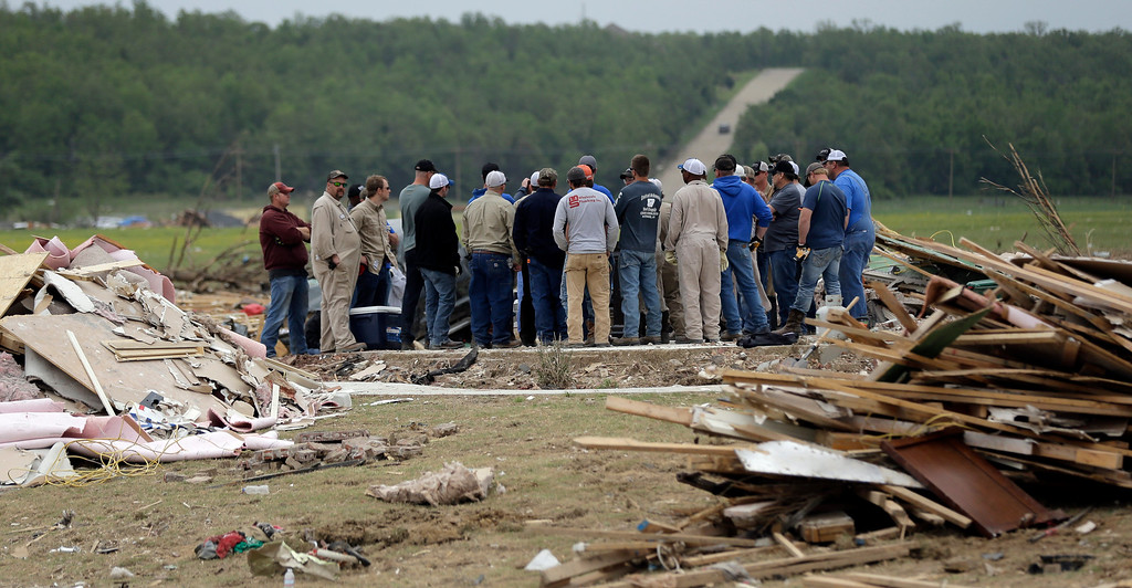 Description of . Volunteers gather on the slab of a home destroyed by Sunday's tornado, Tuesday, April 29, 2014, in Vilonia, Ark. (AP Photo/Eric Gay)