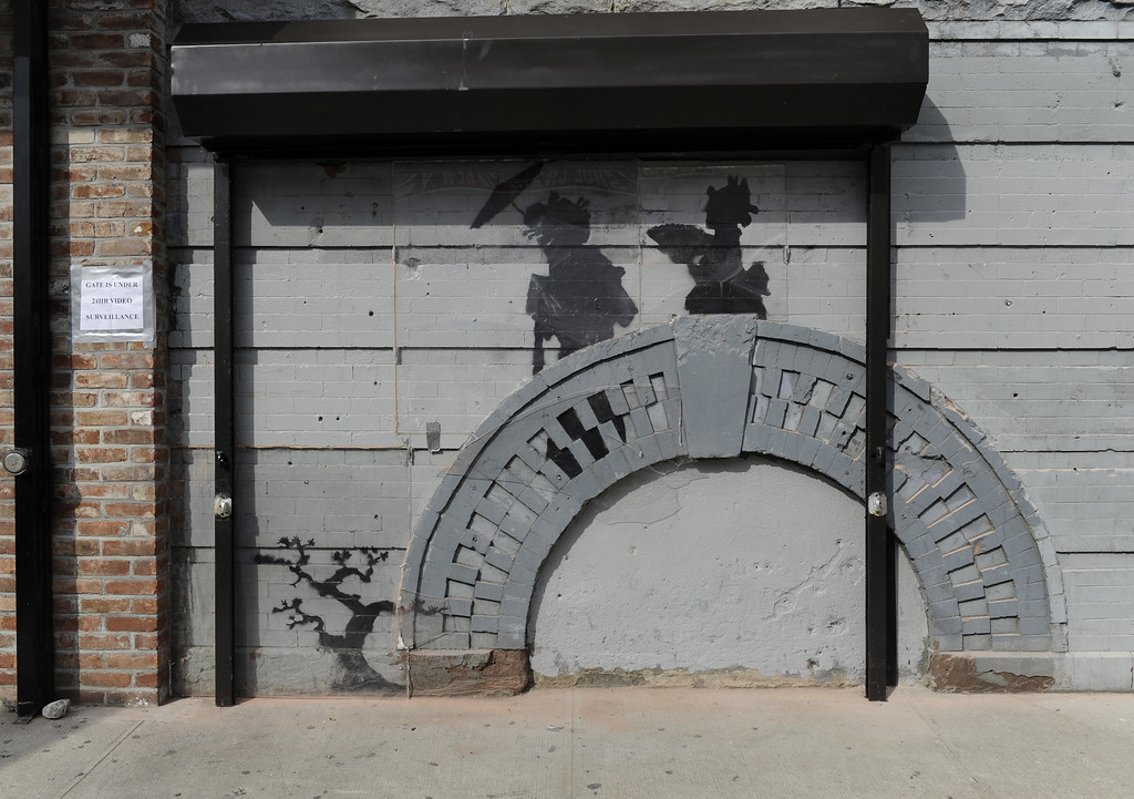Description of . Work by British graffiti artist Banksy is displayed on Saturday, Oct. 19, 2013, in the Brooklyn borough of New York. The building owner has hired security guards and installed a metal gate to protect a work by Banksy. Cara Tabachnick, whose family owns the building, said the goal is to preserve the artwork