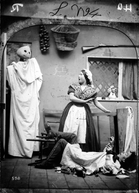 Description of . circa 1865:  A white caped figure wearing a haloween pumpkin mask taking two people by surprise in their kitchen.  London Stereoscopic Company Comic Series - 598  (Photo by London Stereoscopic Company/Getty Images)