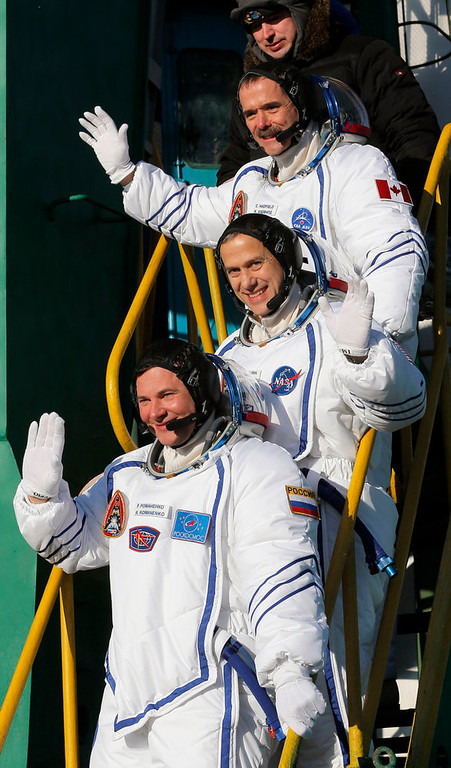 Description of . International Space Station crew members U.S. astronaut Thomas Marshburn (C), Russian cosmonaut Roman Romanenko (bottom) and Canadian astronaut Chris Hadfield wave as they board the Soyuz TMA-07M spacecraft at the Baikonur cosmodrome December 19, 2012.  REUTERS/Dmitry Lovetsky/Pool