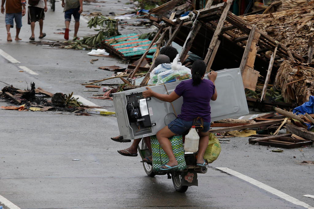Description of . A resident holds a refrigerator as they drive home Tuesday, Nov. 12, 2013 in Tacloban city in, Leyte province in central Philippines. Four days after Typhoon Haiyan devastated islands in the central Philippines, survivors are desperate for food and clamoring to be evacuated. (AP Photo/Bullit Marquez)