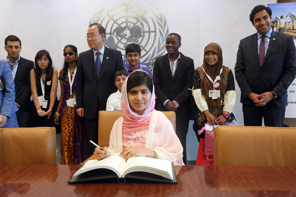 Description of . Malala Yousafzai signs United Nations Secretary-General Ban Ki-moon\'s guest books as Ban Ki-moon, center, and youth delegates look on, Friday, July 12, 2013 at United Nations headquarters. Malala Yousafzai, the Pakistani teenager shot by the Taliban for promoting education for girls, will celebrated her 16th birthday on Friday addressing the United Nations. (AP Photo/Mary Altaffer)