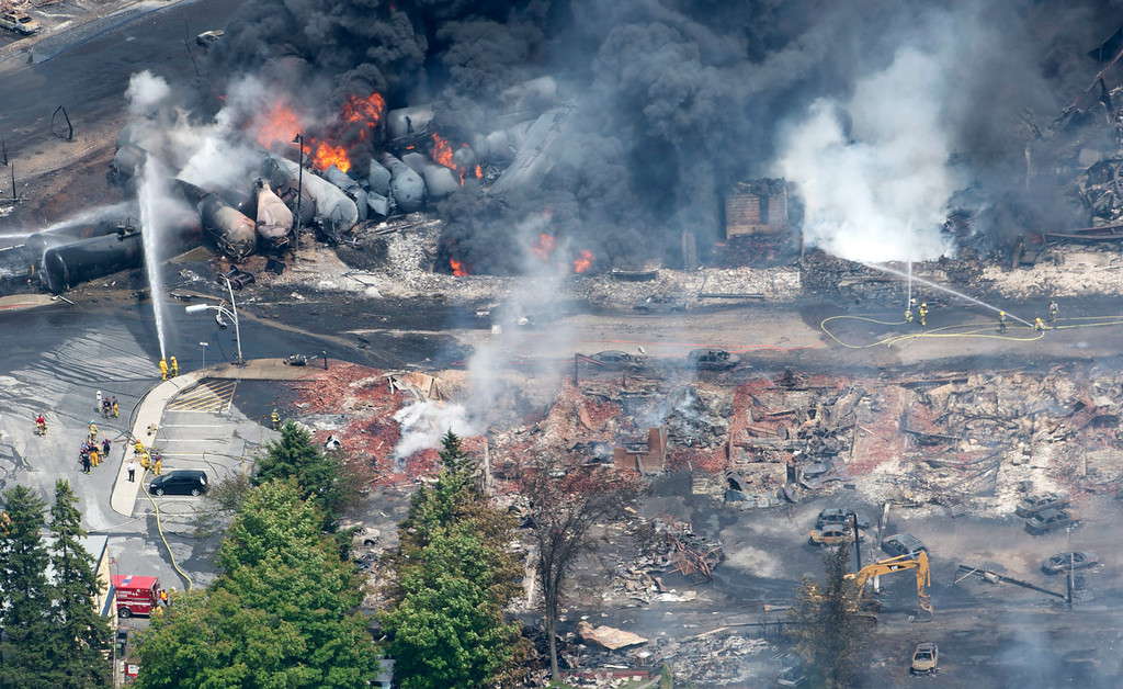Description of . Smoke rises from railway cars that were carrying crude oil after derailing in downtown Lac Megantic, Que., Saturday, July 6, 2013. A large swath of Lac Megantic was destroyed Saturday after a train carrying crude oil derailed, sparking several explosions and forcing the evacuation of up to 1,000 people. (AP Photo/The Canadian Press, Paul Chiasson)