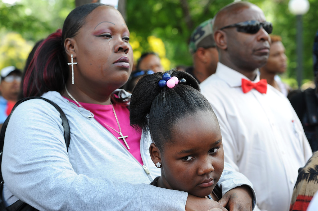 Description of . Torri Morris, 11, stays close in the arms of her mother Tamesah Morris, during the rally in City Park in Denver, CO on July 14, 2013.  Members of the African American community turned out for a rally  to show their disappointment in the acquittal of George Zimmerman in the murder trail of Trayvon Martin on July 14, 2013. Zimmerman is the Florida man who shot and killed Trayvon Martin.
