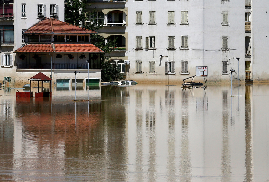 Description of . Buildings are reflected in a flooded street in Obrenovac, some 30 kilometers (18 miles) southwest of Belgrade, Serbia, Monday, May 19, 2014. Belgrade braced for a river surge Monday that threatened to inundate Serbia's main power plant and cause major power cuts in the crisis-stricken country as the Balkans struggle with the consequences of the worst flooding in southeastern Europe in more than a century. At least 35 people have died in Serbia and Bosnia in the five days of flooding caused by unprecedented torrential rain, laying waste to entire towns and villages and sending tens of thousands of people out of their homes, authorities said. (AP Photo/Darko Vojinovic)