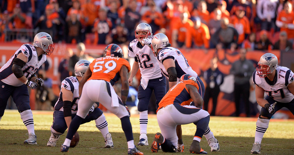 Description of . New England Patriots quarterback Tom Brady (12) yells the call at his teammates during the third quarter. The Denver Broncos vs. The New England Patriots in an AFC Championship game  at Sports Authority Field at Mile High in Denver on January 19, 2014. (Photo by John Leyba/The Denver Post)