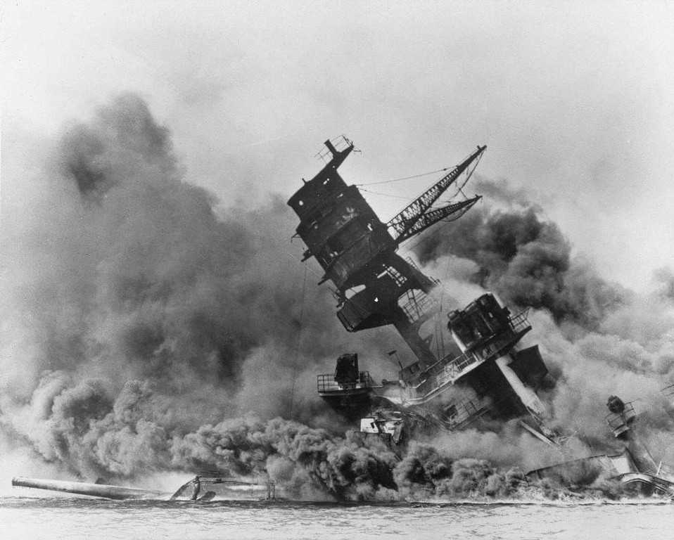 Description of . The battleship USS Arizona belches smoke as it topples over into the sea during a Japanese surprise attack on Pearl Harbor, Hawaii,  Dec. 7, 1941. The ship sank with more than 80  percent of its 1,500-man crew, including Rear Admiral Isaac C. Kidd . The attack, which left 2,343 Americans dead and 916 missing, broke the backbone of the U.S. Pacific Fleet and forced  America out of a policy of isolationism. President Franklin D. Roosevelt announced that it was