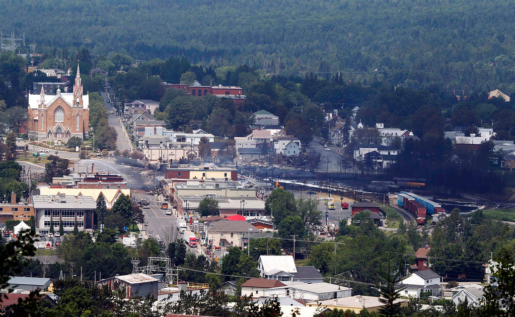 Description of . A view of the town from a lookout point at Lac Megantic, Quebec, July 7, 2013.  A driverless freight train carrying tankers of petroleum products derailed at high speed and exploded into a giant fireball in the middle of the small Canadian town of Lac-Megantic early on Saturday, destroying dozens of buildings and leaving an unknown number of people feared missing.  REUTERS/Christinne Muschi
