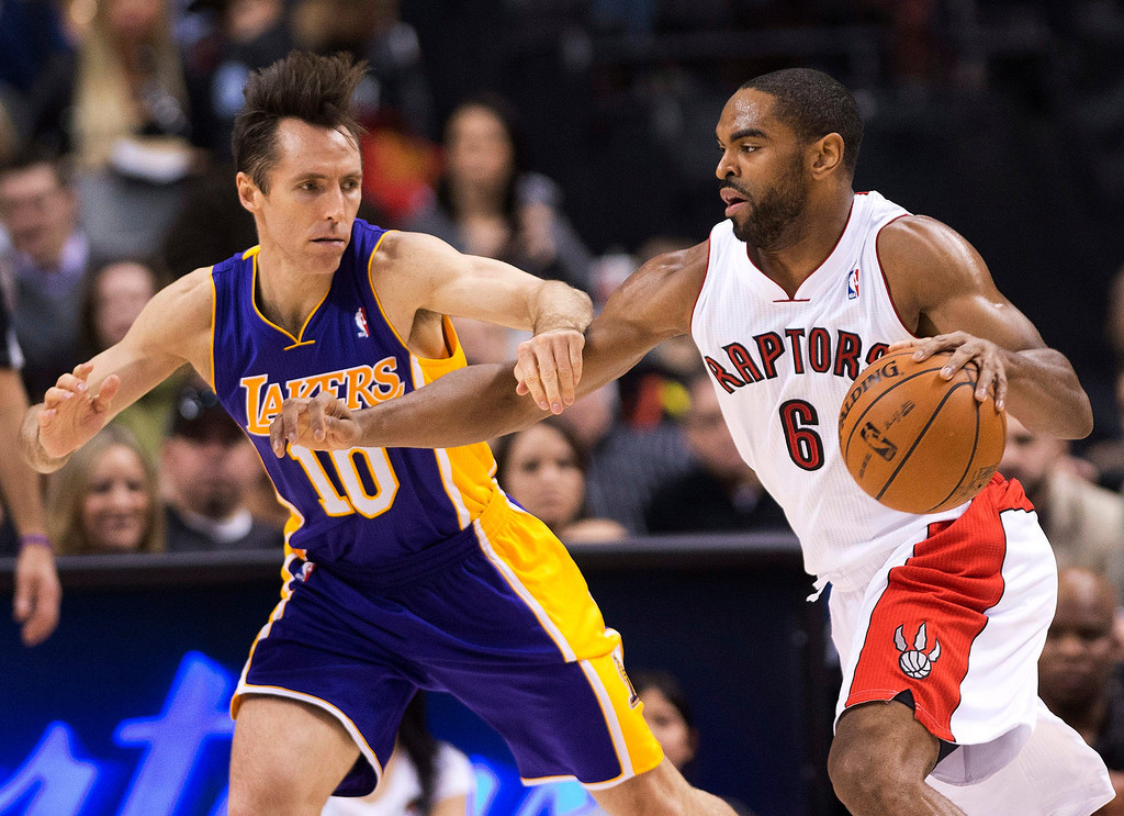 Description of . Los Angeles Lakers guard Steve Nash, left, applies pressure on Toronto Raptors forward Alan Anderson, right, during first half NBA basketball action in Toronto on Sunday Jan. 20, 2013. (AP Photo/THE CANADIAN PRESS,Nathan Denette)