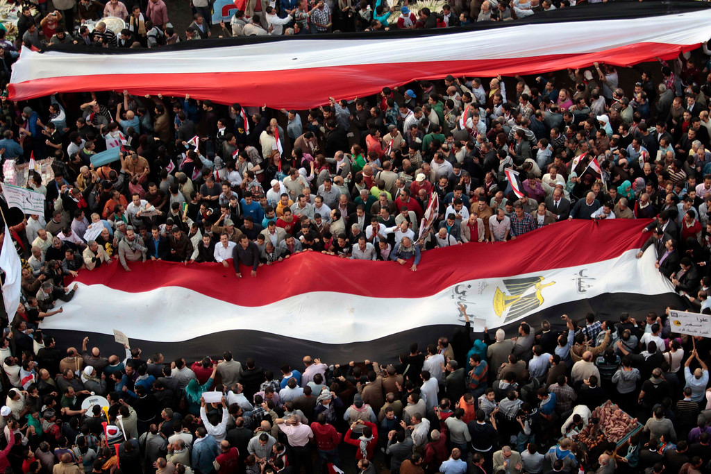 Description of . Anti-Mursi protesters display large Egyptian flags while chanting anti-government and anti-Muslim Brotherhood slogans at Tahrir Square in Cairo November 27, 2012. Opponents of President Mohamed Mursi rallied in Cairo's Tahrir Square for a fifth day on Tuesday, stepping up calls to scrap a decree they say threatens Egypt with a new era of autocracy. REUTERS/Ahmed Jadallah