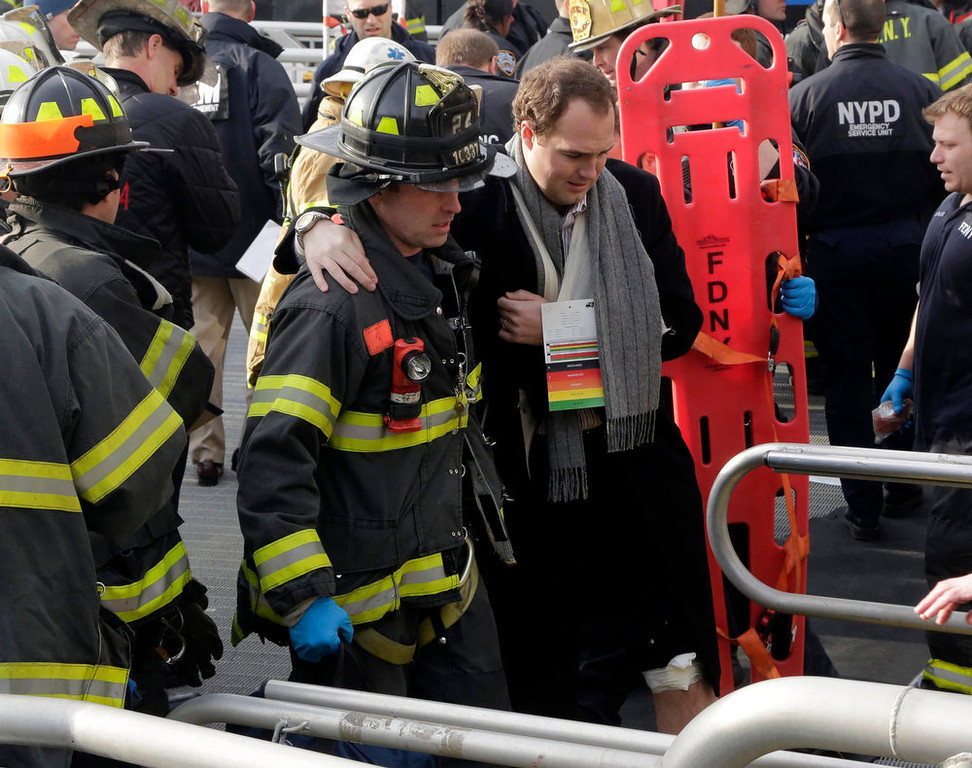 Description of . An injured passenger from the Seastreak Wall Street ferry is taken to an ambulance, in New York,  Wednesday, Jan. 9, 2013. The  ferry from Atlantic Highlands, N.J., banged into the mooring as it arrived at South Street in lower Manhattan during morning rush hour, injuring as many as 50 people, at least one critically, officials said.(AP Photo/Richard Drew)