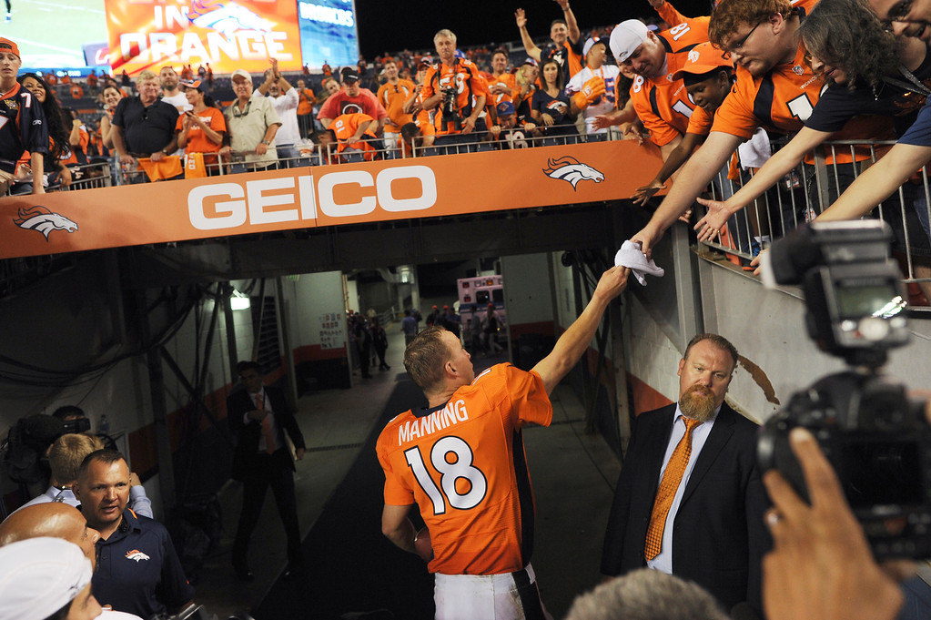 Description of . Denver Broncos quarterback Peyton Manning (18) greets fans after the Broncos defeated the Ravens 49-24. Denver Broncos Baltimore Ravens September 5, 2013 at Sports Authority at Mile High. (Photo by Joe Amon/The Denver Post)