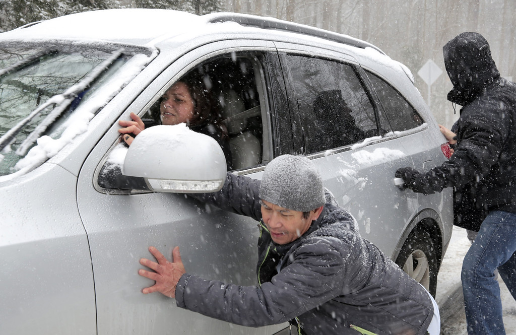 Description of . Melanie Ridlon gets help up a slick hill along Seawell School Rd. in Chapel Hill, NC, during a snow storm on Wednesday, Feb. 12, 2014.  Several cars, including a school bus, were stranded on the hill as snow continued to fall.  (AP Photo/Ted Richardson)