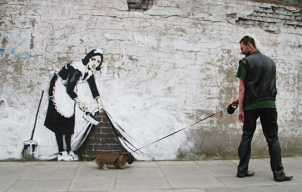 Description of . Grafitti art by the 'guerilla' artist Banksy is seen on May 16, 2006 in Chalk Farm, London. The striking large scale spray-painted image entitled 'Sweeping It Under The Carpet' depicts a maid who cleaned the artist's room in a motel in Los Angeles. The piece commissioned by 'The Independent' newspaper edited on Tuesday by U2's frontman Bono, is intended to represent a metaphor for the west's reluctance to tackle issues such as Aids in Africa.  (Photo by Dave Etheridge-Barnes/Getty Images)