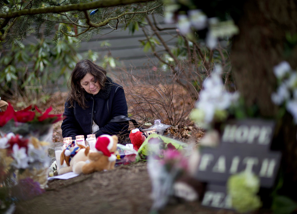 Description of . Dilma Steiner, of Newtown, Conn., visits a sidewalk memorial for the Sandy Hook Elementary School shooting victims, Sunday, Dec. 16, 2012, in Newtown, Conn. A gunman walked into Sandy Hook Elementary School in Newtown Friday and opened fire, killing 26 people, including 20 children. (AP Photo/David Goldman)