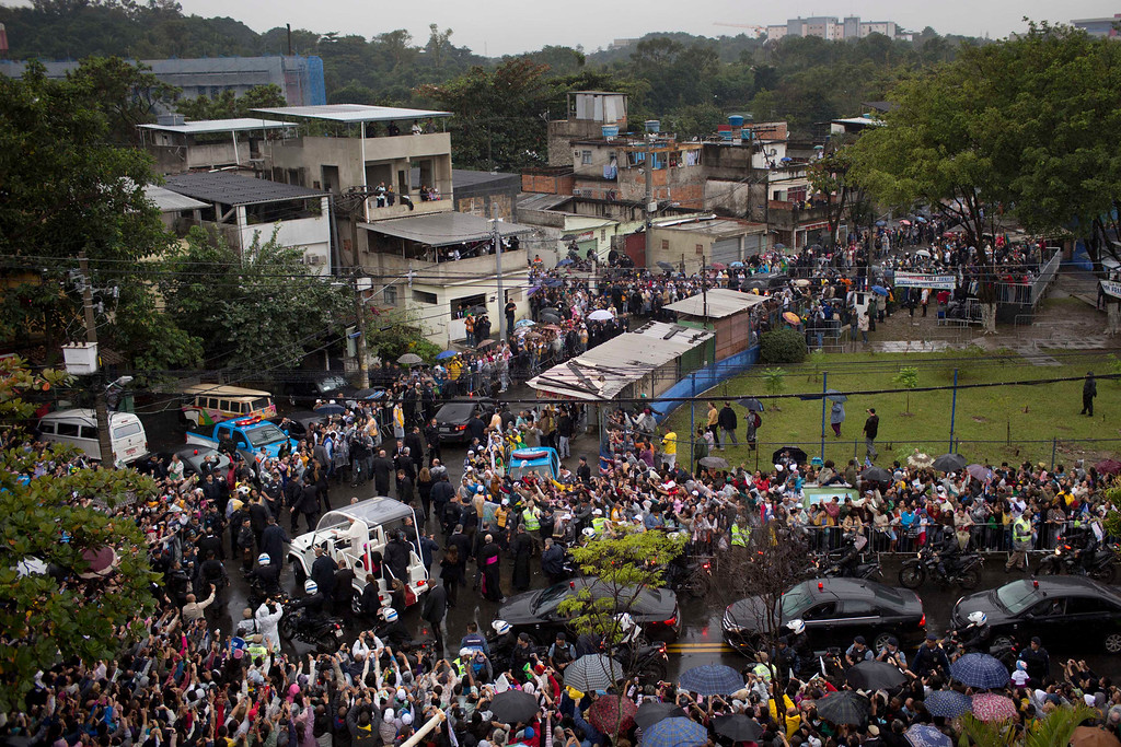 Description of . People line the roads to greet Pope Francis as he arrives in his popemobile to the Varginha slum, part of the Manguinhos slum complex in Rio de Janeiro, Brazil, Thursday, July 25, 2013. Pope Francis on Thursday visited one of Rio de Janeiro's shantytowns, or favelas, a place that saw such rough violence in the past that it's known by locals as the Gaza Strip. (AP Photo/Felipe Dana)
