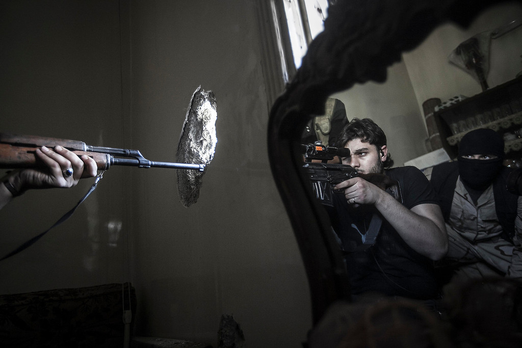 Description of . In this Oct. 29, 2012 file photo, a rebel sniper aims at a Syrian army position, seen with another rebel fighter reflected in a mirror, in a residential building in the Jedida district of Aleppo, Syria. (AP Photo/Narciso Contreras, File)