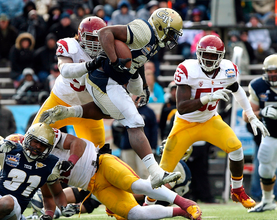 . Georgia Tech running back David Sims, top, leaps over a pile up of Southern California defenders during the Sun Bowl NCAA college football game, Monday, Dec. 31, 2012, in El Paso, Texas. Georgia Tech won 21-7. (AP Photo/Mark Lambie)