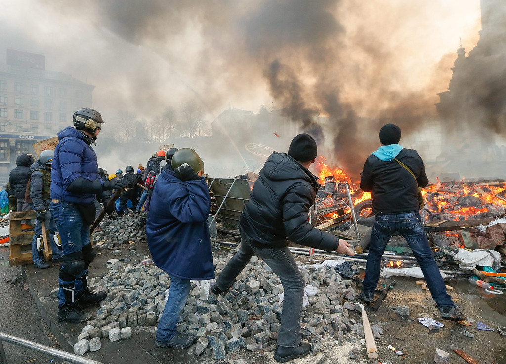 Description of . Protesters throw stones as they clash with riot police during on-going anti-government protests in downtown Kiev, Ukraine, 19 February 2014.  EPA/SERGEY DOLZHENKO