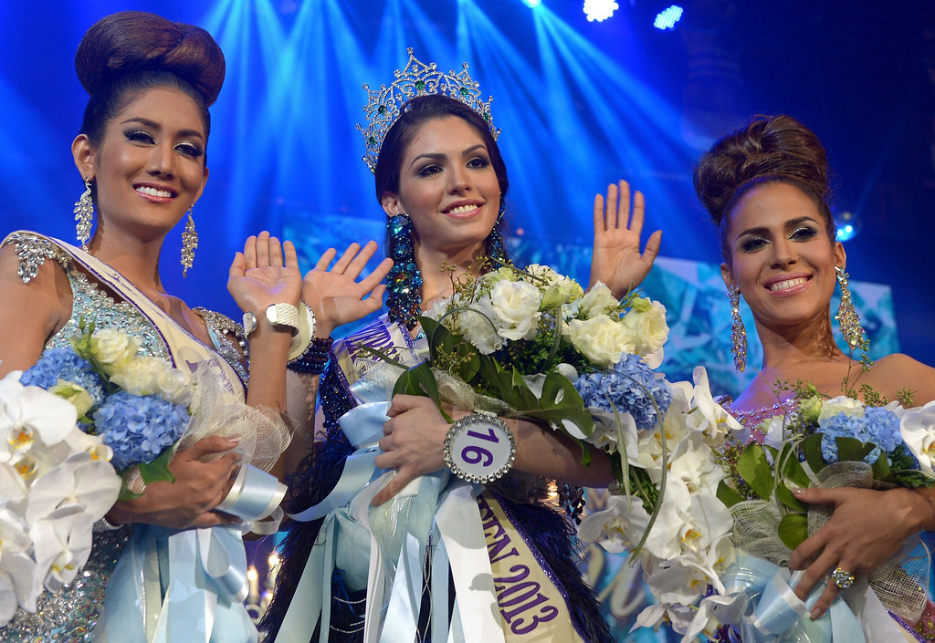 Description of . Marcelo Ohio of Brazil (C) waves next to first runner up Shantell D' Marco of US (R) and second runner up Nethnapada Kanrayanon of Thailand (L) after winning the International Queen 2013 Transexual beauty contest in Pattaya on November 1, 2013. Twenty-five contestants from 17 countries competed in Pattaya for the Miss International Queen title.        AFP PHOTO / PORNCHAI  KITTIWONGSAKUL/AFP/Getty Images
