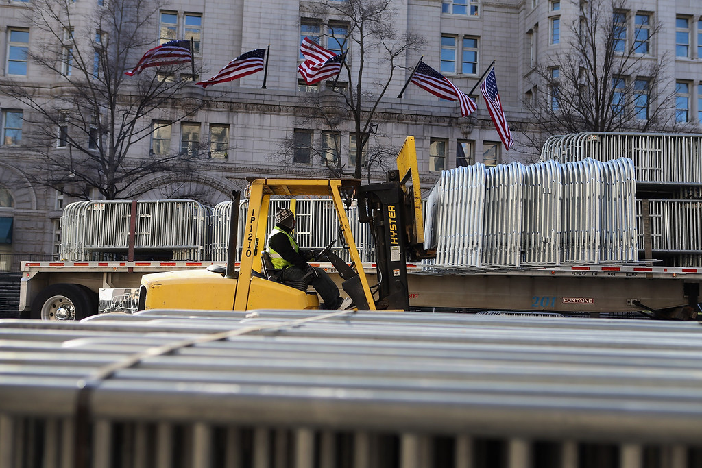 Description of . A worker moves security fences into position along Pennsylvania Ave as preparations continue for the Inauguration Parade on January 20, 2013 in Washington, DC.  The US capital is preparing for the second inauguration of US President Barack Obama, which will take place on January 21.  (Photo by Joe Raedle/Getty Images)