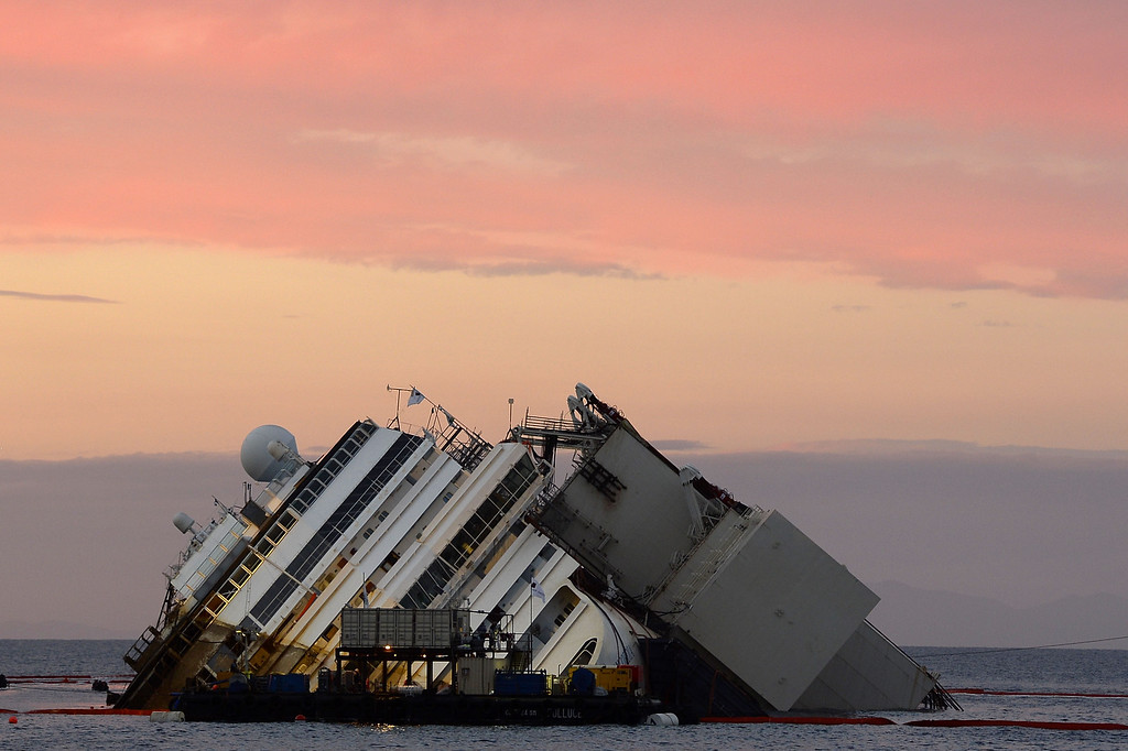 Description of . Italy's Costa Concordia cruise ship during sunset near the harbor of Giglio Porto as it is slowly uprighted on September 16, 2013. Salvage workers attempt to raise the cruise ship tonight, in the largest and most expensive maritime salvage operation in history, so-called