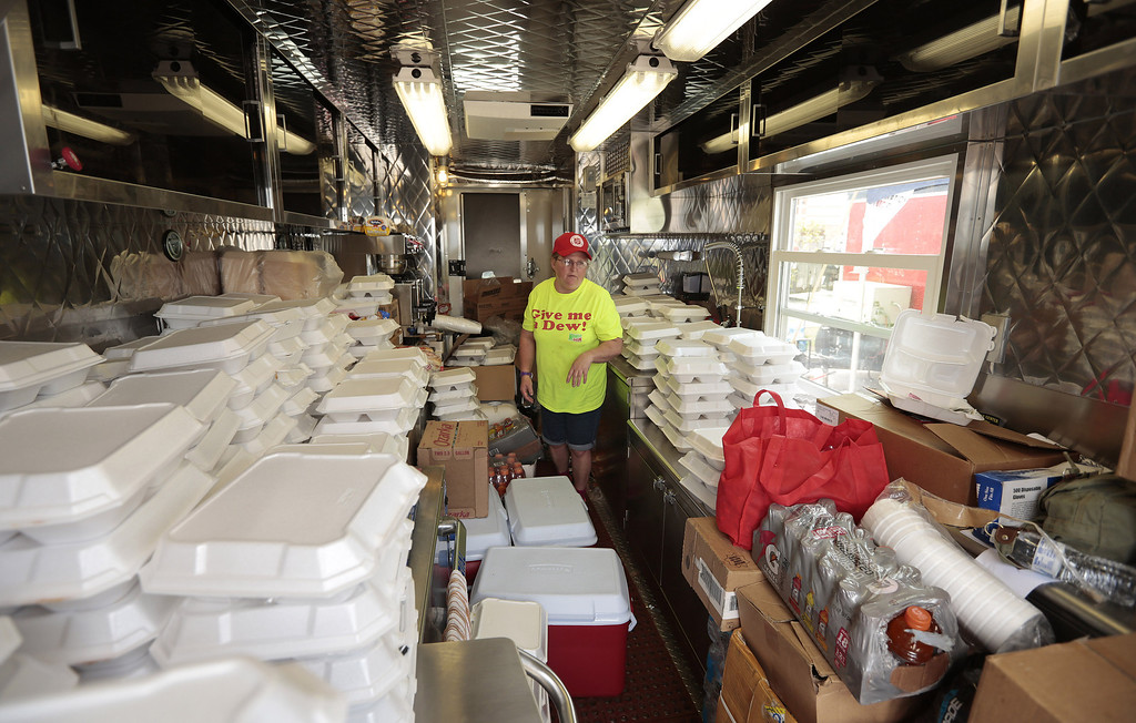 Description of . MOORE, OK -  MAY 23:  Salvation Army volunteer Mary Watts checks the load of food ready for distribution to victims of the May 20 tornado May 23, 2013  in Moore, Oklahoma. The tornado of at least EF4 strength and up to two miles wide touched down May 20 killing at least 24 people and leaving behind extensive damage to homes and businesses. U.S. President Barack Obama promised federal aid to supplement state and local recovery efforts.    (Photo by Brett Deering/Getty Images)