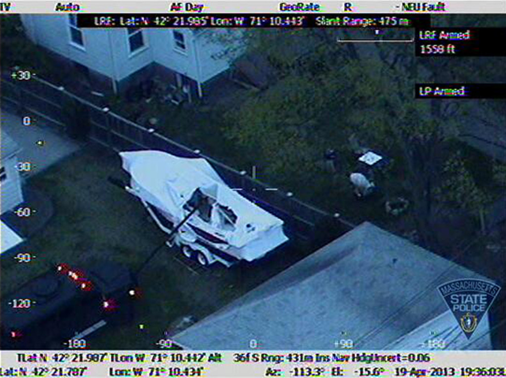 Description of . This Friday, April 19, 2013 image made available by the Massachusetts State Police shows a police vehicle probing the boat where 19-year-old Boston Marathon bombing suspect, Dzhokhar Tsarnaev, was hiding in Watertown, Mass. He was pulled, wounded and bloody, from the boat parked in the backyard of a home in the Greater Boston area. (AP Photo/Massachusetts State Police)