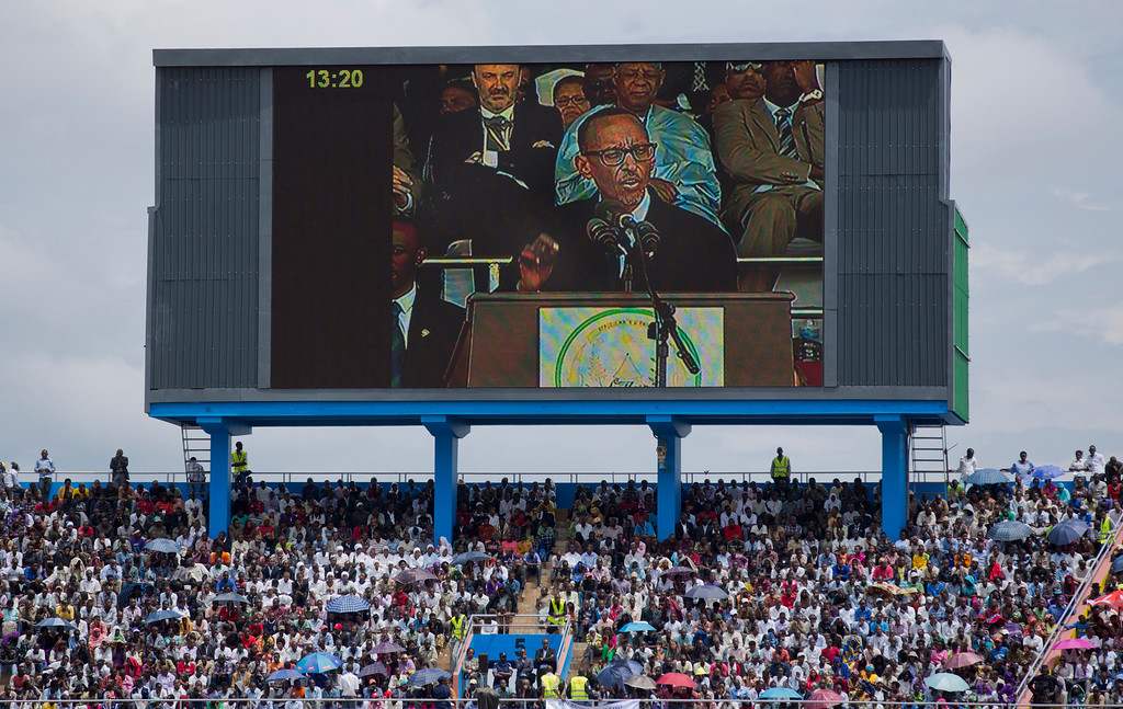 Description of . Rwandan President Paul Kagame, seen on a large television screen, addresses the public and dignitaries at a ceremony to mark the 20th anniversary of the Rwandan genocide, at Amahoro stadium in Kigali, Rwanda Monday, April 7, 2014.  (AP Photo/Ben Curtis)