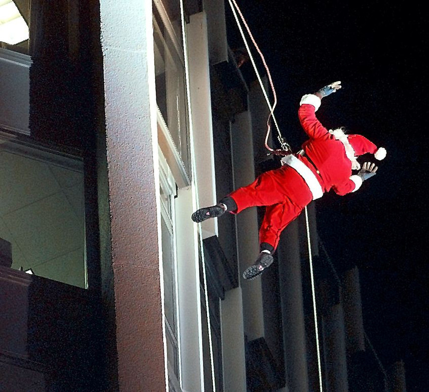 Description of . A climber dressed as Santa Claus foregoes his normal transportation of reindeers and a sleigh and rappels down the side of the Landmark Office Building in downtown Stamford, Connecticut 11 December during a pre-Christmas event. AFP PHOTO/Timothy CLARY