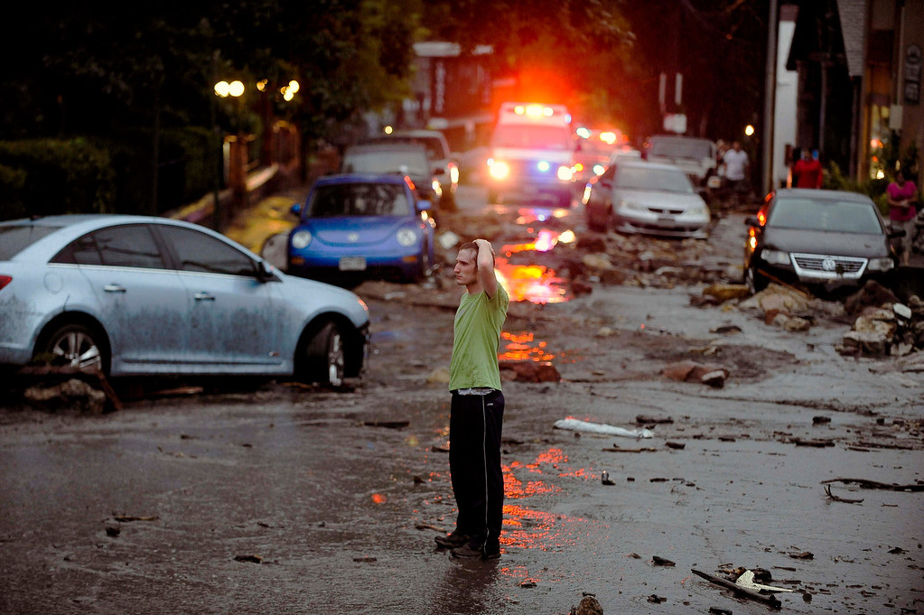 Description of . Carson Dennis stands in the middle of the destruction caused by a flash flood that poured down Canon Avenue, Friday, Aug. 9, 2013 in Manitou, Colo.  (AP Photo/The Colorado Springs Gazette, Michael Ciaglo)