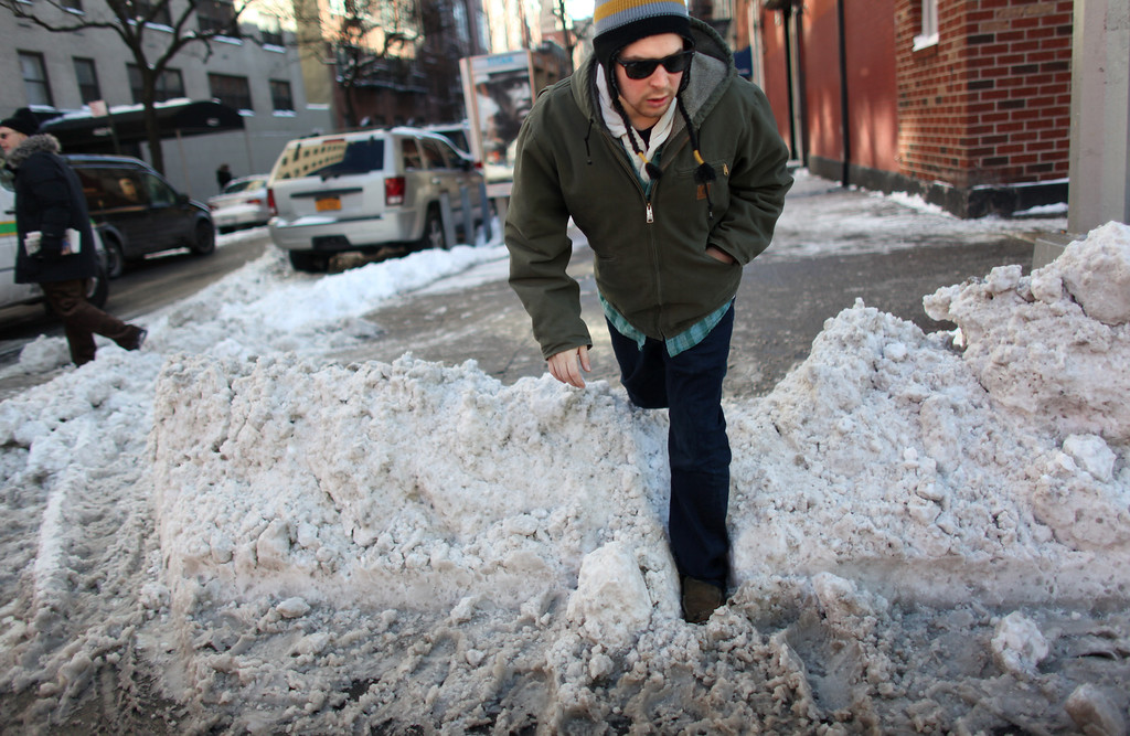 Description of . A man jumps over a pile of snow to cross 1st Ave. after an overnight storm dropped up to 7 inches of snow on January 04, 2014 in New York City. The Northeast and Midwest regions of the United States were hit with a large amount of snowfall accompanied by blizzard-like winds and plummeting temperatures this week. (Photo by Yana Paskova/Getty Images)