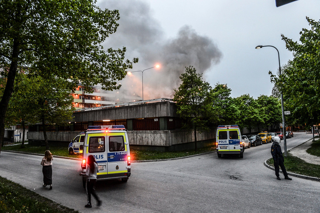 Description of . Policemen secure an apartment building after youths rioted in Husby, northern Stockholm on May 20, 2013. Youths in the immigrant-heavy Stockholm suburb of Husby torched cars and threw rocks at police, in riots believed to be linked to the deadly police shooting of a local resident. An apartment building had to be evacuated for an hour during the night after fire spread inside a garage, and shops and schools in the low-income neighbourhood had their windows crashed. FREDRIK SANDBERG/AFP/Getty Images