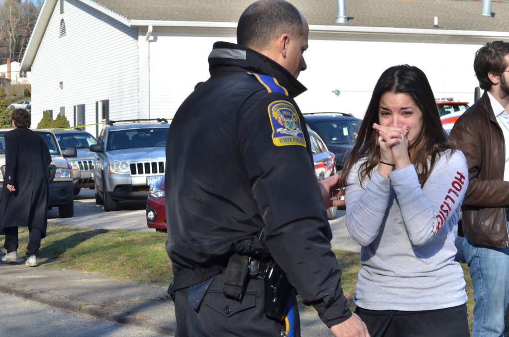 Description of . An unidentified woman asks a police officer for information about a teacher after a shooting spree threw Sandy Hook Elementary School in Newtown into turmoil Friday morning. Melanie Stengel/Register