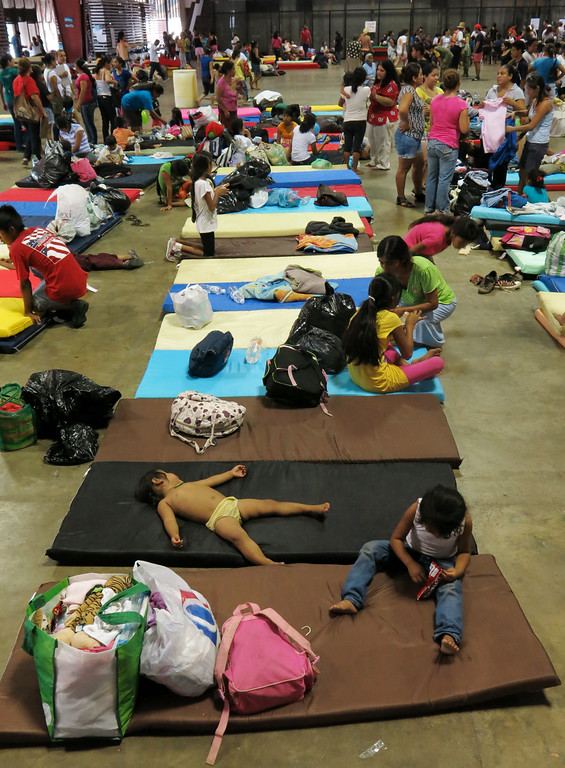 Description of . Residents from the village La Pintada rest inside the Acapulco Convention Center after their town was affected by flooding, in Acapulco, Mexico, Thursday, Sept. 19, 2013.  (AP Photo/Michael Weissenstein)