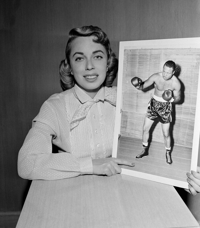 Description of . Dr. Joyce Brothers, child psychologist, who hit the $64,000 jackpot in quiz on boxing knowledge, with photo of Boxer Archie Moore July 22, 1956. (AP Photo/Jacon Harris)