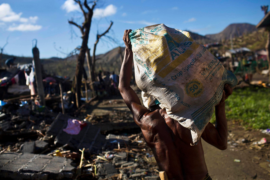 Description of . A Typhoon Haiyan survivor carries a bag of his recovered belongings in the ruins of his rural neighborhood on the outskirts of Tacloban, Philippines on Monday Nov. 18, 2013. Hundreds of thousands of people were displaced by Typhoon Haiyan, which tore across several islands in the eastern Philippines on Nov. 8. (AP Photo/David Guttenfelder)