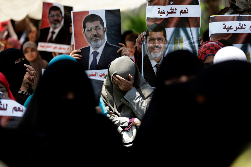 Description of . A supporter of ousted Egypt's President Mohammed Morsi cries during a protest near the University of Cairo, Giza, Egypt, Friday, July 5, 2013. Arabic reads,