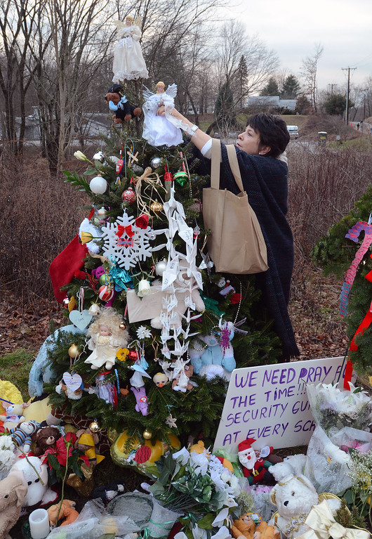 Description of . Staff photos by Tom Kelly IV William Raveis Real Estate employees placed an angel a top each of the 26 Christmas trees for the victims from Sandy Hook Elementary School.  Here, Beth Caldwell, places the angel on one of the trees.  Funerals for two, six year old students from the Sandy Hook Elementary School in Newtown, CT took part Tuesday December 18, 2012.  Mourners paid their respects at the Saint Rose of Lima Church.