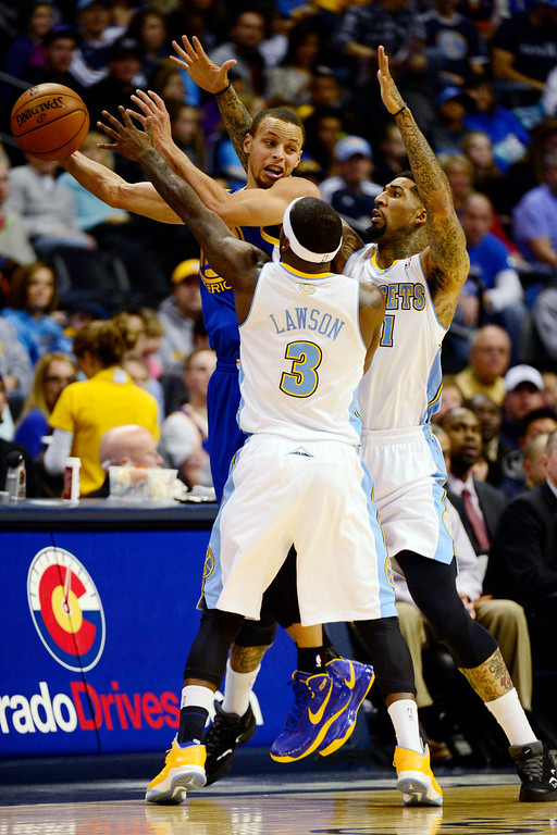 Description of . Golden State Warriors point guard Stephen Curry (30) is pressured by Denver Nuggets point guard Ty Lawson (3) and shooting guard Wilson Chandler (21)  during the first half at the Pepsi Center on Sunday, January 13, 2013. AAron Ontiveroz, The Denver Post