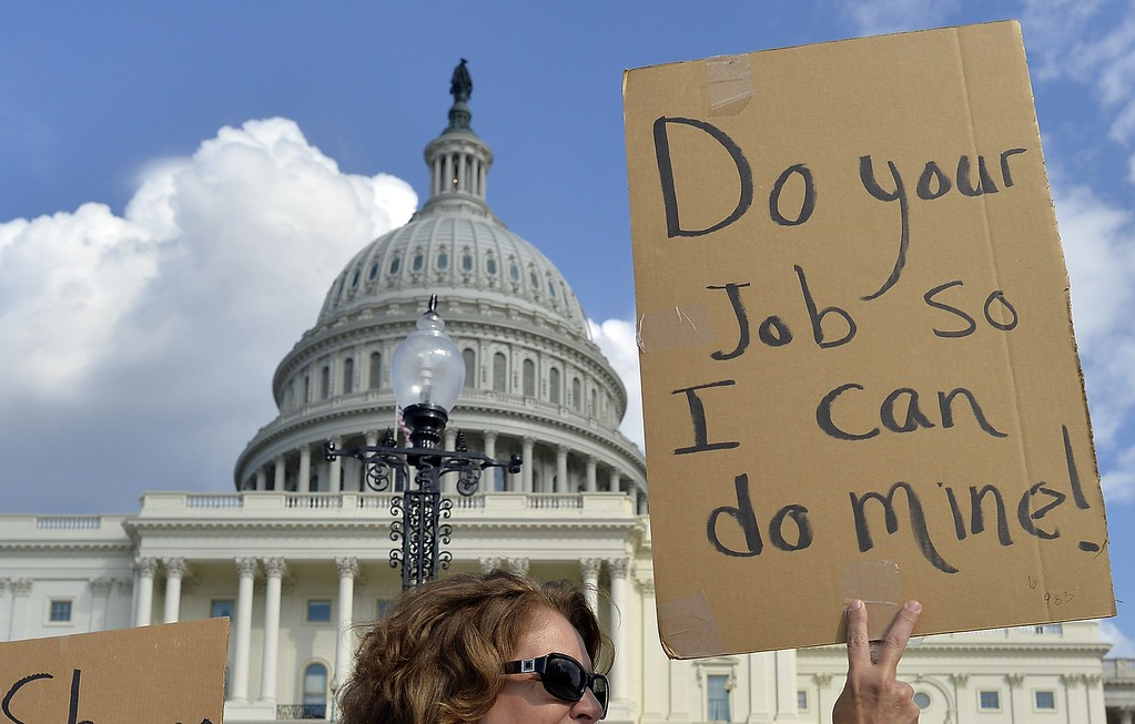 Description of . Protesters display placards during a demonstration in front of the US Capitol in Washington, DC, on October 1, 2013 urging congress to pass the budget bill.  AFP Photo/Jewel  SAMAD/AFP/Getty Images