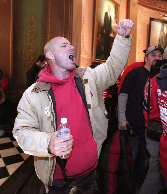 Description of . Union members from around the country march through the rotunda of the Michigan State Capitol to protest a vote on Right-to-Work legislation December 11, 2012 in Lansing, Michigan. Republicans control the Michigan House of Representatives, and Michigan Gov. Rick Snyder has said he will sign the bill if it is passed. The new law would make requiring financial support of a union as a condition of employment illegal. (Photo by Bill Pugliano/Getty Images)