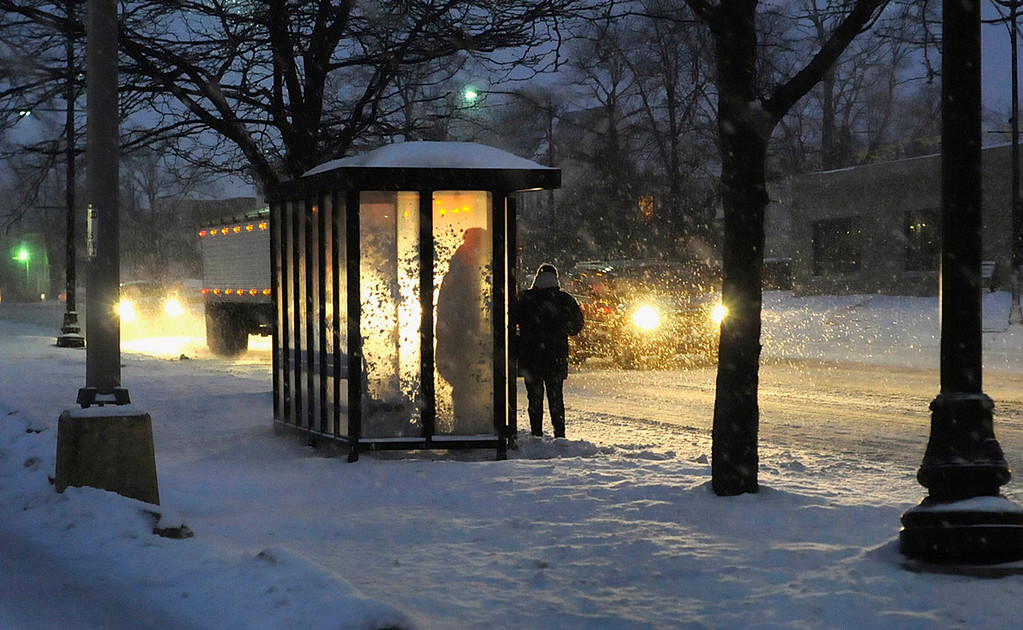Description of . Commuters wait for a River Valley Metro Transit District bus as lake effect snow reaches Kankakee, Ill., before dawn on Thursday morning Jan. 2, 2014. (AP Photo/The Daily Journal, Mike Voss)