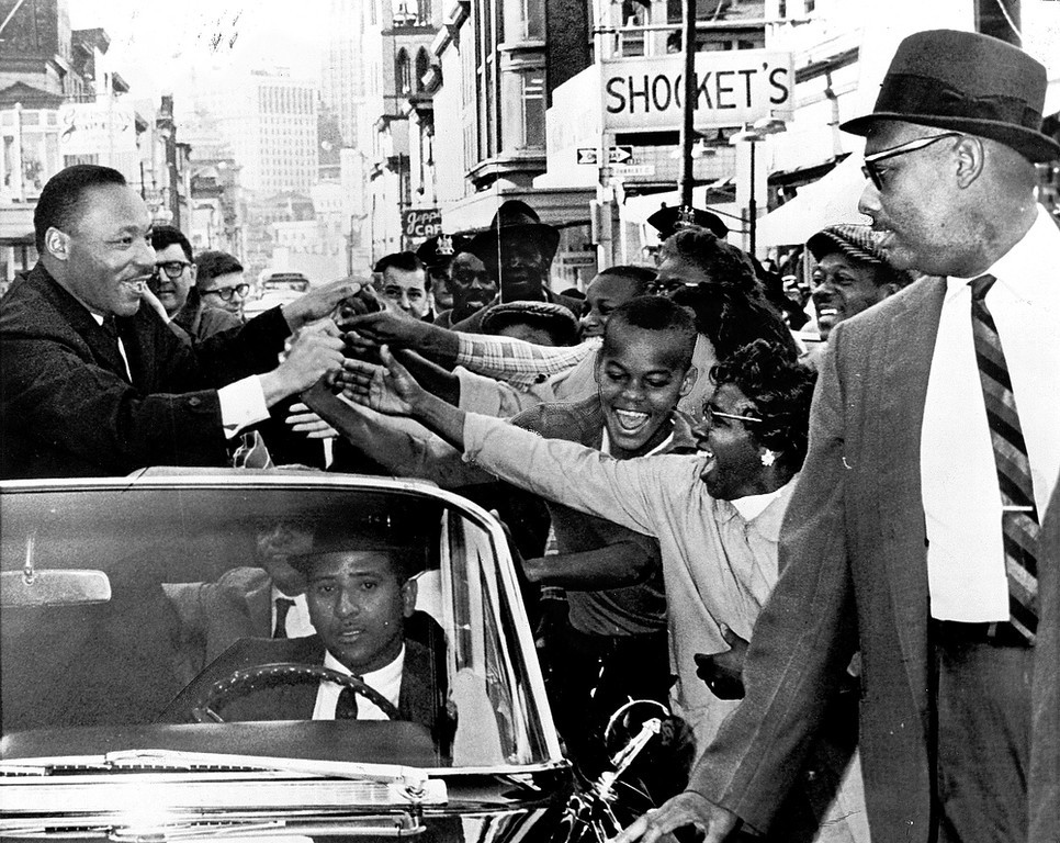Description of . Martin Luther King greets a crowd in Baltimore in 1964.